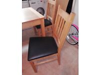 Extending dining table with 6 wooden/faux leather chairs.