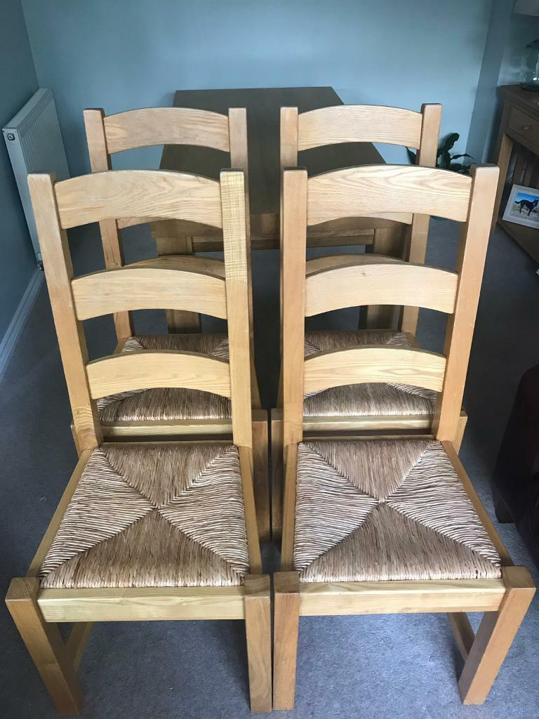 Four solid oak dining kitchen chairs with wicker seat used
