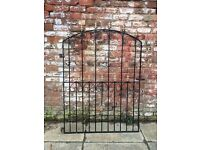 black wrought iron gate with gold finials