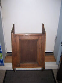 A 1920's HANGING OAK WALL CABINET HAVING SHAPED WATERFALL SUPPORT