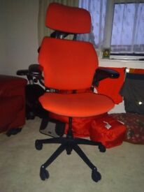 A high quality heavy bright red upholstered chair swivel with gas operated rise and fall.