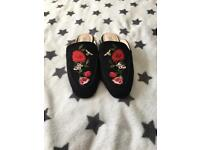 Flat black slip on shoes with floral patern