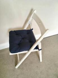 White Ikea wooden folding chair with navy cushion