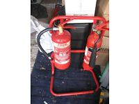 A pair of fire extinguishers on a stand