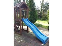 Wooden climbing frame with swing and slide
