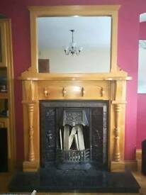 Fireplace surrounding with large mirror and cast iron insert