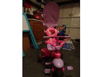 Children pink trike with detachable parent handle and parasol