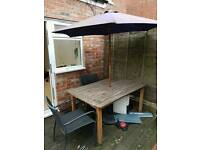 Garden table with parasol and base and chairs