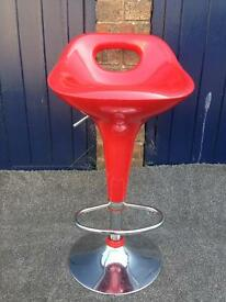 One red breakfast bar stool. (plus a matching one that is cracked, free)