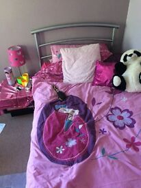 Single metal bed with new mattress and one white metal bunk bed frame without mattresses.