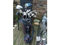 Full set of golf clubs in bag with trolley.