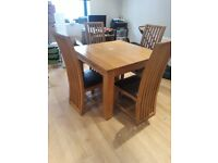 Solid oak table and chairs lobely design slightly damaged but could be repaired .