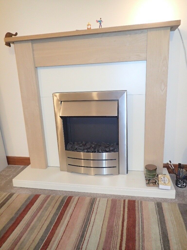 Modern electric fire and fireplace, oak and ivory coloured surround.