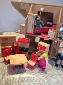 Wooden dolls house with wooden kitchen and bedroom furniture and wooden family figures