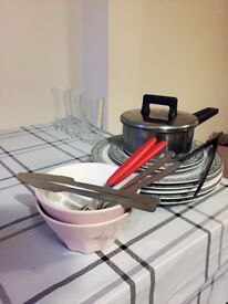 Glass Cups, Bowls, Small and Large Plates, Small Cooking Pot, Plastic Tongs, and Cutlery