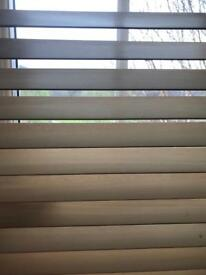 Venetian light coloured wooden blinds.