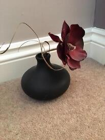 Small black vase with flower