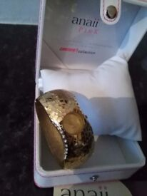 Gold bangle watch in case with leaflet and sparkles