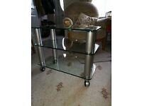 TV stand in glass with metal columns and castors
