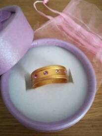 Gold coloured ring with pink stones