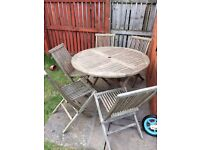 Teak garden dining set with round table and five chairs