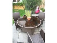 4 seater brown wicker seats and glass table
