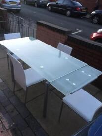 Lovely glass dining table extends out 4 chairs