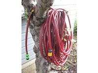 Long red sturdy hosepipe with tap connector
