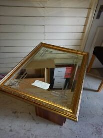 big mirror in gold coloured wood frame