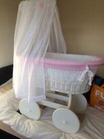 Beautiful wicker crib bigger than the average crib stand has wooden wheels
