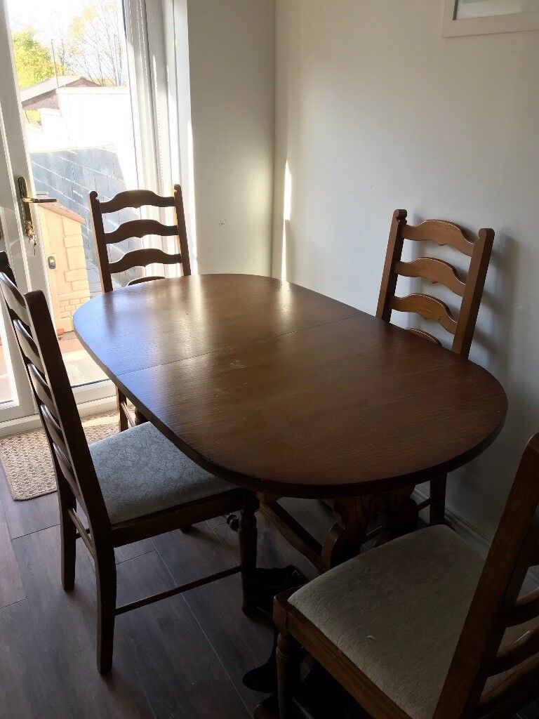 Oak oval dining table and 4 chairs with cream seats.