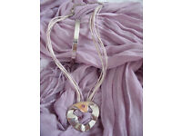 Silver coloured metal bangle and unusual pendant on cord/chain with amethyst coloured stones.£3 both