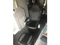 Black leather gaming chair with footstall.