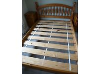 Pine double bed with wood slated base. In very good condition, a solid bed frame.