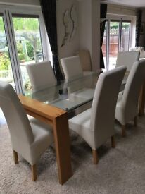 Glass dining table and 6 cream leather chairs