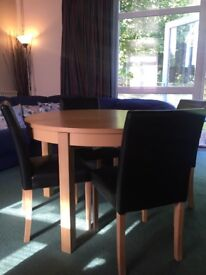 Circular extendable wooden table and four chairs
