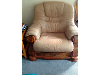 Beige leather lounge suite; 3 str sofa + 1 chair.Carved wood base,small drawer under each seat. £150