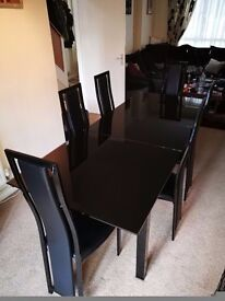 AS NEW EXTENDING BLACK GLASS TABLE AND 6 CHAIRS