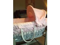 A beautiful grey wicker basket and rocking stand with soft pale pink dimple bedding