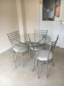 Round, glass table with 3 chairs