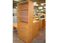 Tall bookcase unit comprising drawers below and shelving above.