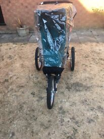Baby jogger with rain over and spare front wheel