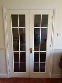 White solid wooden rebated internal glazed door with safety glass and includes handles and hinges..