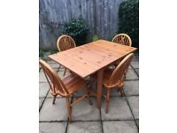 Pine table and chairs with drop leaf sides.