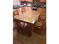 Solid wood dining table with 8 chairs. 1.8m x 1.0m complete with 5mm laminated glass top