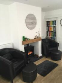 Pair of faux leather tubs chairs with matching footstools and cushions