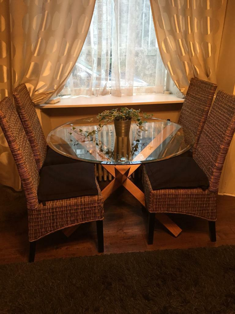 Glass Circular Dining Table On Crossed Oak Veneer Legs With Four Rattan Chairs