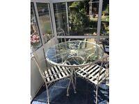 Marks and Spencer round glass table and 4 chairs, hardly used, plus chair pads
