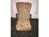 Upholstered arm chair with wooden arms which lift to receive chair