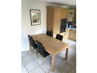 Solid Oak Dinning table with 4 high rise leather chairs.